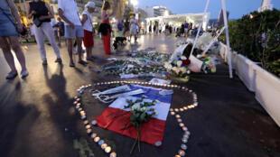 """法國尼斯""""英國人步行大道""""上,民眾向2016年國慶日被一伊斯蘭極端分子駕瘋狂卡車衝撞碾斃死難者紀念碑致哀。  2017年7月14日"""