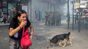 Une étudiante tente d'échapper à du gaz lacrymogène, lors de manifestations en lien avec la réforme de l'éducation au Chili, à Santiago, le 25 avril 2019.