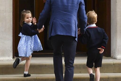 La princesse Charlotte salue la foule avant d'entrer avec son père William et son frère George à la maternité St. Mary, le 23 avril 2018.
