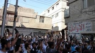 eople protest against President Bashar al-Assad on the first day of Eid Al-Fitr in the city of Suqba August 30, 2011