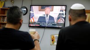 Israelíes escuchan una alocusión televisada de Donald Trump, en un café de Ashkelón (Israël), el 8 de mayo de 2018.