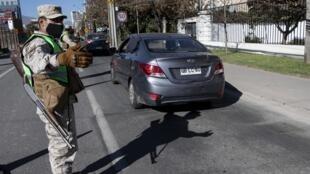 Soldado chileno controla viaturas em  Santiago, onde foi decretado o confinamento total a partir de 16 de Maio de 2020.