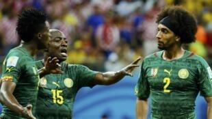 Achille Webo (katikati) akijaribu kuwaamua wachezaji wenzake Benjamin Moukando (Kushoto) aliyekuwa akitaka kupigana na Benoît Assou-Ekotto.