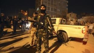 Benghazi, 3 mai 2011. Un insurgé bloque la rue après l'explosion d'une voiture piégée non loin du tribunal de la ville, qui sert de lieu de réunion au Conseil national de transition.