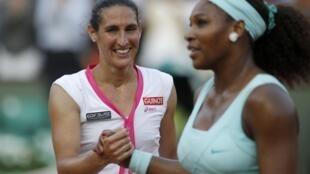 Virginie Razzano shakes hands with Serena Williams after winning her match