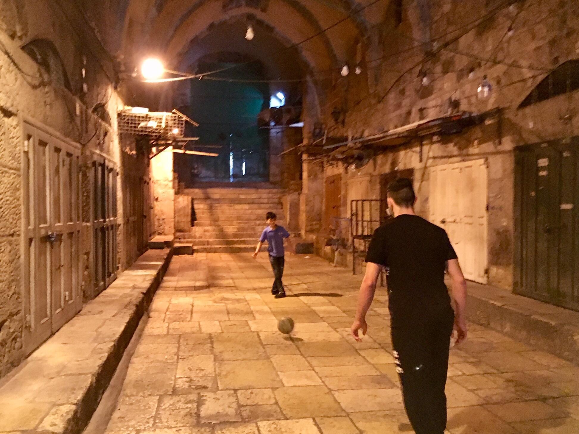 兩名年輕人在耶路撒冷老城的一條空無一人的小巷裡踢足球,齋月即將開始時,所有商店都關門了。