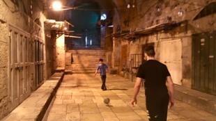 两名年轻人在耶路撒冷老城的一条空无一人的小巷里踢足球,斋月即将开始时,所有商店都关门了。