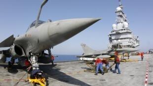 Một tên lửa được lắp vào chiến đấu cơ Rafale trên hàng không mẫy hạm Charles de Gaulle của Pháp ngày 27/3/2011.