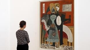 """A visitor looks at the painting """"The Lovers"""" as the Picasso museum"""