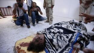 Visitantes fotografam o corpo do ex-ditador Muammar Kadafi, exposto na cidade de Misrata.