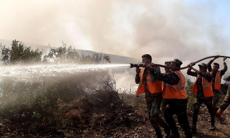 Les pompiers finissant d'éteindre un incendie à Safita, en Syrie.