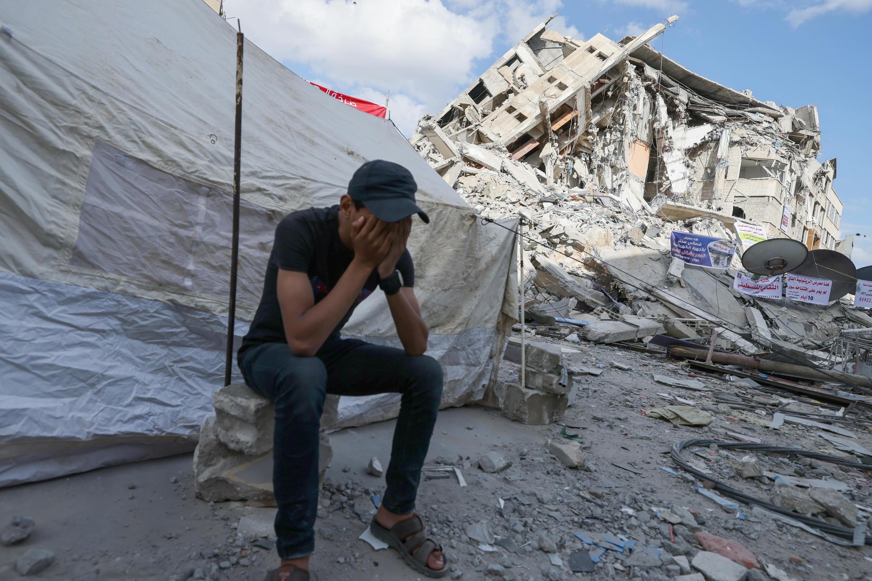 Un palestino cubre su rostro con las manos, sentado ante una carpa instalada entre escombros en la Franja de Gaza, el 23 de mayo de 2021