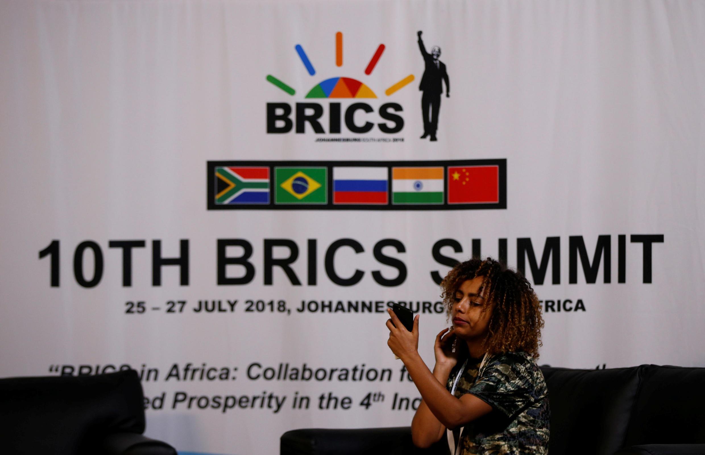 Mulher faz selfie em frente a cartaz do 10° do Brics, em Sandton, África do Sul, em julho de 2018.
