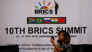 ស្ត្រីម្នាក់កំពុងមើលទូស័ព្ទដៃរបស់ខ្លួននៅពីមុខស្លាកសញ្ញានៃជំនួបកំ ពូលនៃក្រុមប្រទេស BRICS  នៅ Sandton ក្នុង អាហ្វ្រិកខាងត្បូងថ្ងៃទី ២៤កក្កដាឆ្នាំ ២០១៨