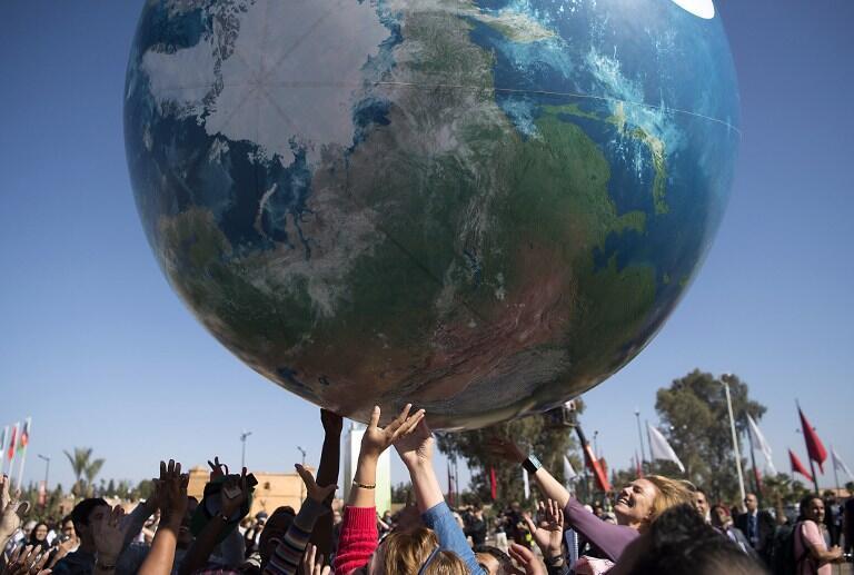 Les membres des délégations internationales jouent avec un ballon géant à l'extérieur de la conférence climatique COP22 le 18 novembre 2016, à Marrakech au Maroc.