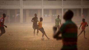 Des enfants jouent au football dans la cour d'une école utilisée comme centre électoral lors de la présidentielle et des législatives du 14 février 2016 à Bangui, RCA.