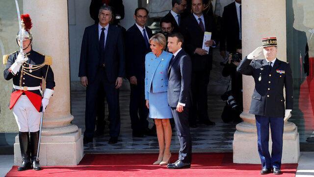 Brigitte e Emmanuel Macron aguardam a saída do carro que leva embora o socialista François Hollande do Palácio do Eliseu.