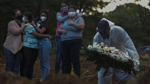 Relatives of a victim of the novel coronavirus disease COVID-19 mourn as their loved one is buried at the Vila Formosa cemetery in Sao Paulo, Brazil, on March 31, 2021