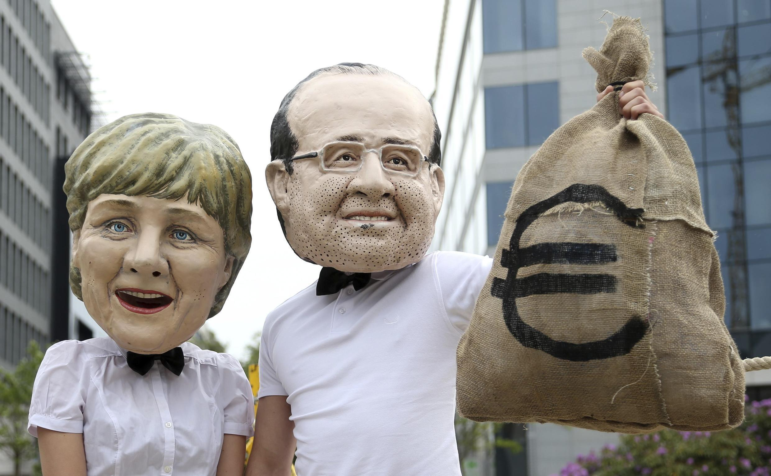 Activists wearing masks depicting German Chancellor Angela Merkel (L) and French President François Hollande back the tax outside the finance ministers' meeting