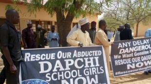 Le 14 mars 2018 à Dapchi, des Nigérians transportent des panneaux lors de la visite du chef de l'Etat, pour réclamer le retour des 110 jeunes filles enlevées.
