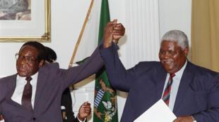 22 décembre 1987. Symbole de réconciliation, Robert Mugabe à la tête de la Zanu, se tient aux côtés de Joshua Nkomo, ancien président de la Zapu. De cette réconciliation, va naître la Zanu-PF.