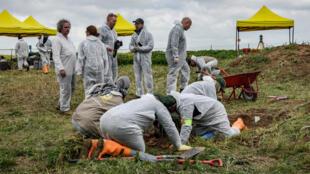 Des médecins légistes et des experts inspectent une zone lors de l'exhumation d'une fosse commune de victimes Yézidis tués par des militants du groupe État islamique, dans le village de Kojo, dans le district de Sinjar (nord de l'Irak), le 15 mars 2019.