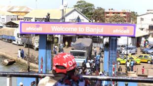 Un passager regarde depuis le pont d'un bateau, qui arrive au port terminal de Banjul, dans la capitale gambienne, le 8 avril 2017.