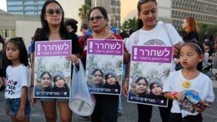 Des enfants philippins et leurs mères tiennent une banderole portant l'inscription en hébreu «libérer la mère philippine et son fils» lors d'une manifestation contre leur expulsion à Tel-Aviv, le 6 août 2019.