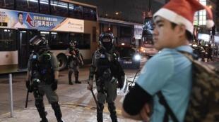 Un homme avec un déguisement du père Noël devant des policiers anti-émeutes à Hong Kong, le 25 décembre 2019.