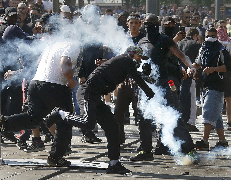 Youths throw stones at riot police in Paris's Place de la République on Saturday