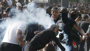 Youths throw stones at riot police in Paris's Place de la République on Saturday