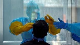 Un médecin prélève de la matière d'un Indien pour le tester, dans le cadre de la lutte contre l'épidémie de coronavirus, à Chennai, le 13 avril 2020.