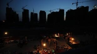 Các công nhân nhập cư tại một công trường xây dựng ở Thượng Hải đang xem những món hàng rẻ tiền bày bán gần khu nhà trọ của họ. Ảnh chụp ngày 02/07/2013.