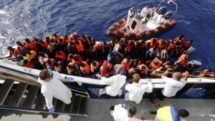 """Группу мигрантов из Африки поднимают на борт итальянского спасательного судна """"Феникс"""" в 25 милях от побережья Ливии 04/10/2014"""