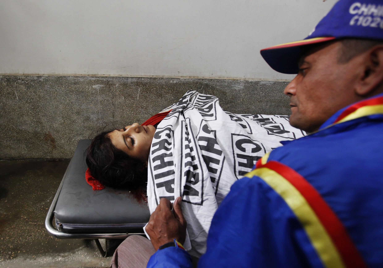 Un sauveteur, devant le corps sans vie d'une des membres de l'équipe de vaccination anti-pilio tuée ce mardi 22 janvier à Karachi, au Pakistan.