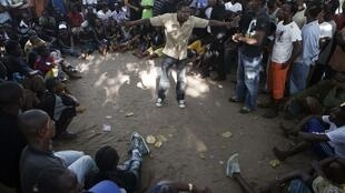 Supporters of Liberia's opposition Congress for Democratic Change party gather under a tree for political discussions