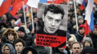 """Los manifestantes de la marcha opositora del 1° de marzo enarbolaron fotos de Boris Nemtsov, asesinado dos días antes. """"Estas balas están dirigidas a cada uno de nosotros"""", dice el cartel."""