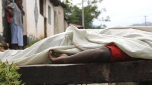 Des habitants regardent le corps d'un homme tué dans le quartier de Nyakabiga, à Bujumbura, le 12 décembre 2015. Les affrontements de vendredi à Bujumbura, la capitale du Burundi, ont fait 87 morts, a annoncé l'armée.