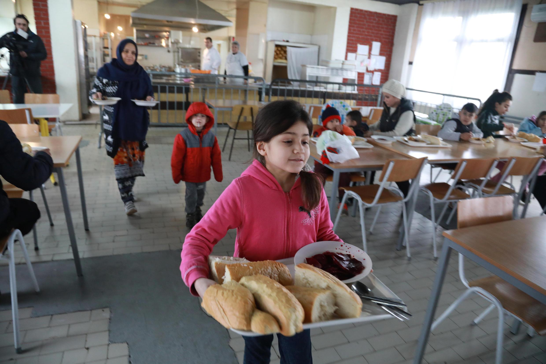 Une petite fille transporte de la nourriture dans le camp pour réfugiés et migrants de Krnjaca, en Serbie, le 16 janvier 2018.