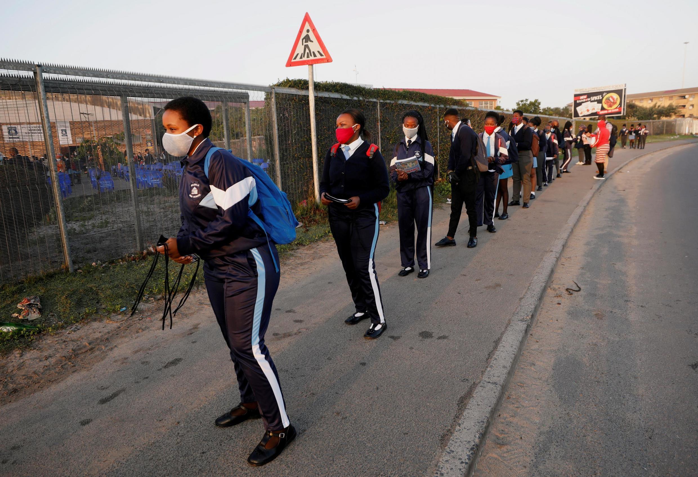 Des écoliers font la queue devant leur école le jour de sa réouverture à Cape Town en Afrique du Sud le 8 juin 2020.