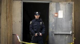 Policial bloqueia a entrada do prédio em Manhattan onde uma possível parte de um dos aviões que se chocou contra o World Trade Center em 2001 foi encontrada neste sábado, dia 27 de abril.