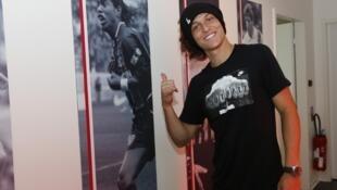David Luiz posa ao lado de foto de Ronaldinho Gaúcho na sede do PSG