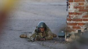 Selon le photographe de Reuters, ce soldat est Ukrainien et dirige son arme vers des manifestants pro-russes, rassemblés sur l'aérodrome de Kramatorsk, le 15 avril 2014.