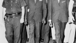 Patrice Lumumba, président du Conseil de la République du Congo, quitte l'aéroport d'Idlewild à New York le 24 juillet 1960, escorté par les policiers américains. L'indépendance du Congo a été proclamé le 30 juin 1960.