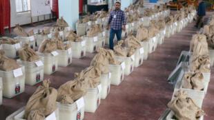 Materiais de votação, incluindo urnas, são vistos dentro de um centro de distribuição antes da 11ª eleição geral, que será realizada em 30 de dezembro em Dhaka