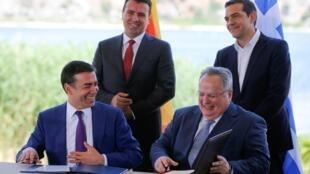 El ministro de exteriores griego, , Nikos Kotzias y su par macedonio, Nikola Dimitrov firman el aciuerdo que oficializa el nombre de Macedonia del Norte, en Psarades, Grecia. Atrás  aparecen los primeros minsitros Alexis Tsipras y Zoran Zaev; 17 de junio 2