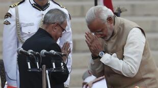 Le nouveau Premier ministre indien Narendra Modi (d) salue le président Pranab Mukherjee, après la cérémonie d'investiture, le 26 mai 2014.