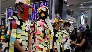 数百港人2019年7月26日在香港机场大厅集会,抗议7•21 元朗暴力事件。示威者仿照列侬墙,在身上贴满写有抗议留言的彩色纸条。