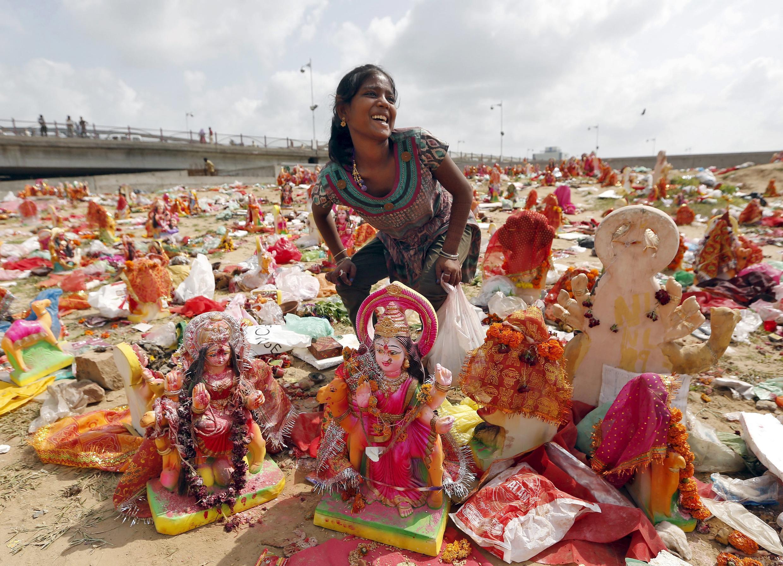 Une jeune Indienne récupère des statuettes de la déesse Dashama, abandonnées par les dévots sur les rives de la rivière Sabarmati au dernier jour du festival pour la déesse. Ahmedabad, le 24 août 2015.