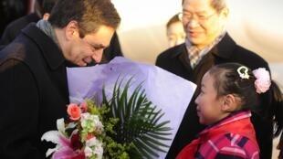 Le Premier ministre français, François Fillon, recevant un bouquet de fleurs d'une petite Chinoise, à son arrivée à l'aéroport de Pékin, le 20 décembre 2009.